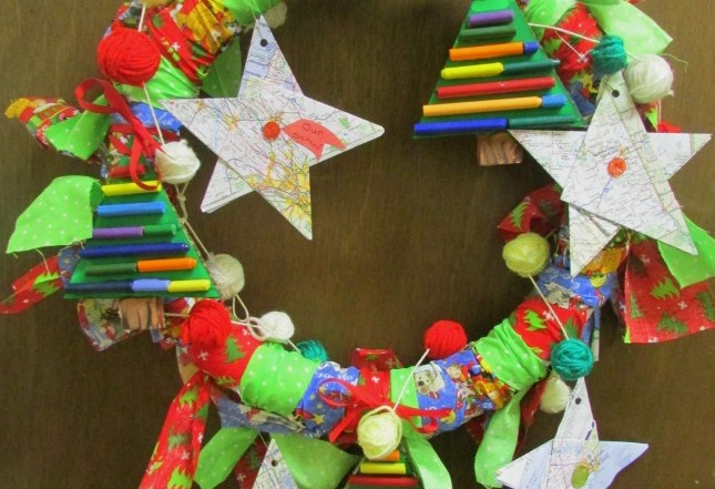 Collaborative holiday wreath made by students from recycled materials