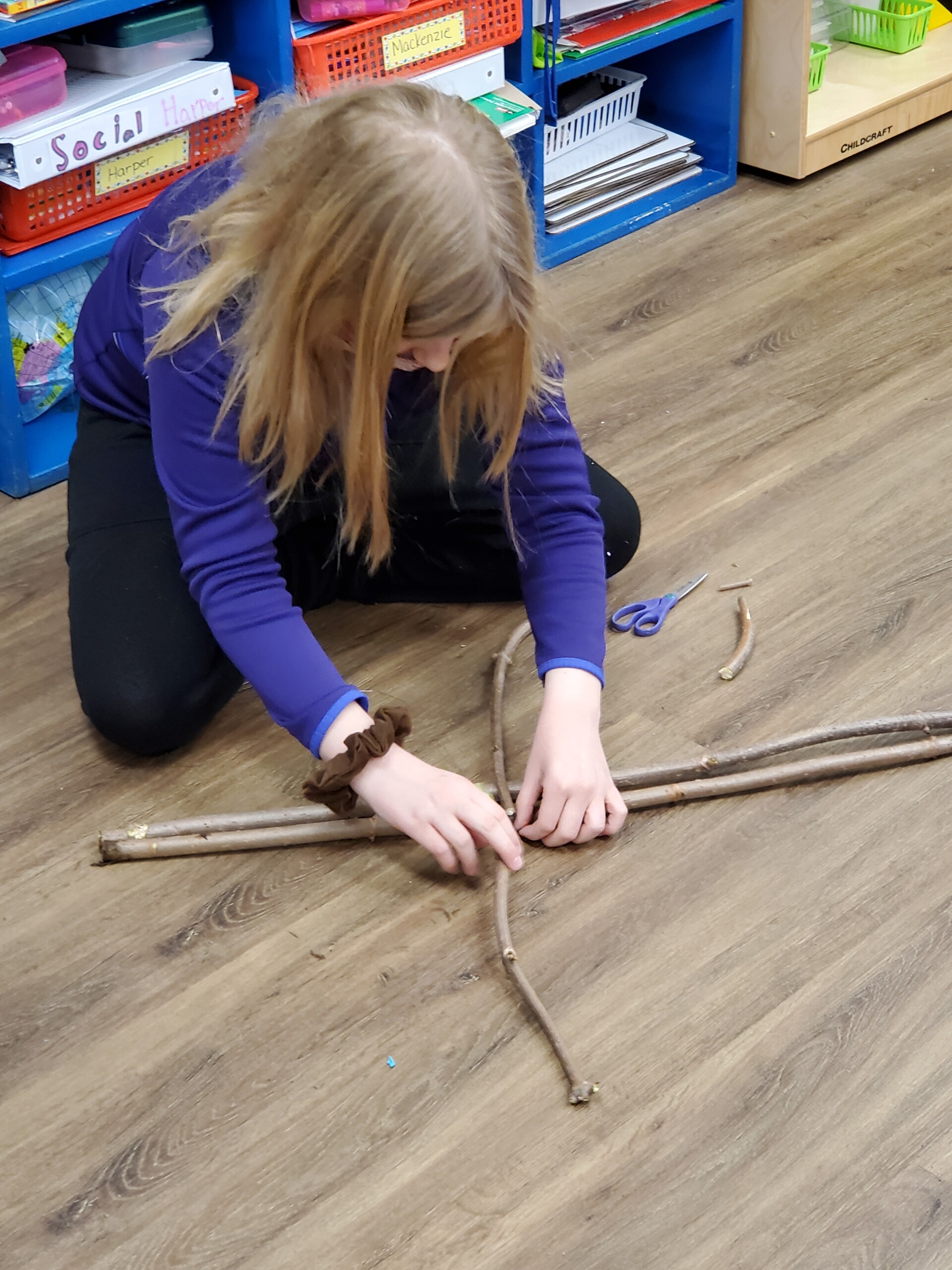 Student creating a scarecrow using sticks