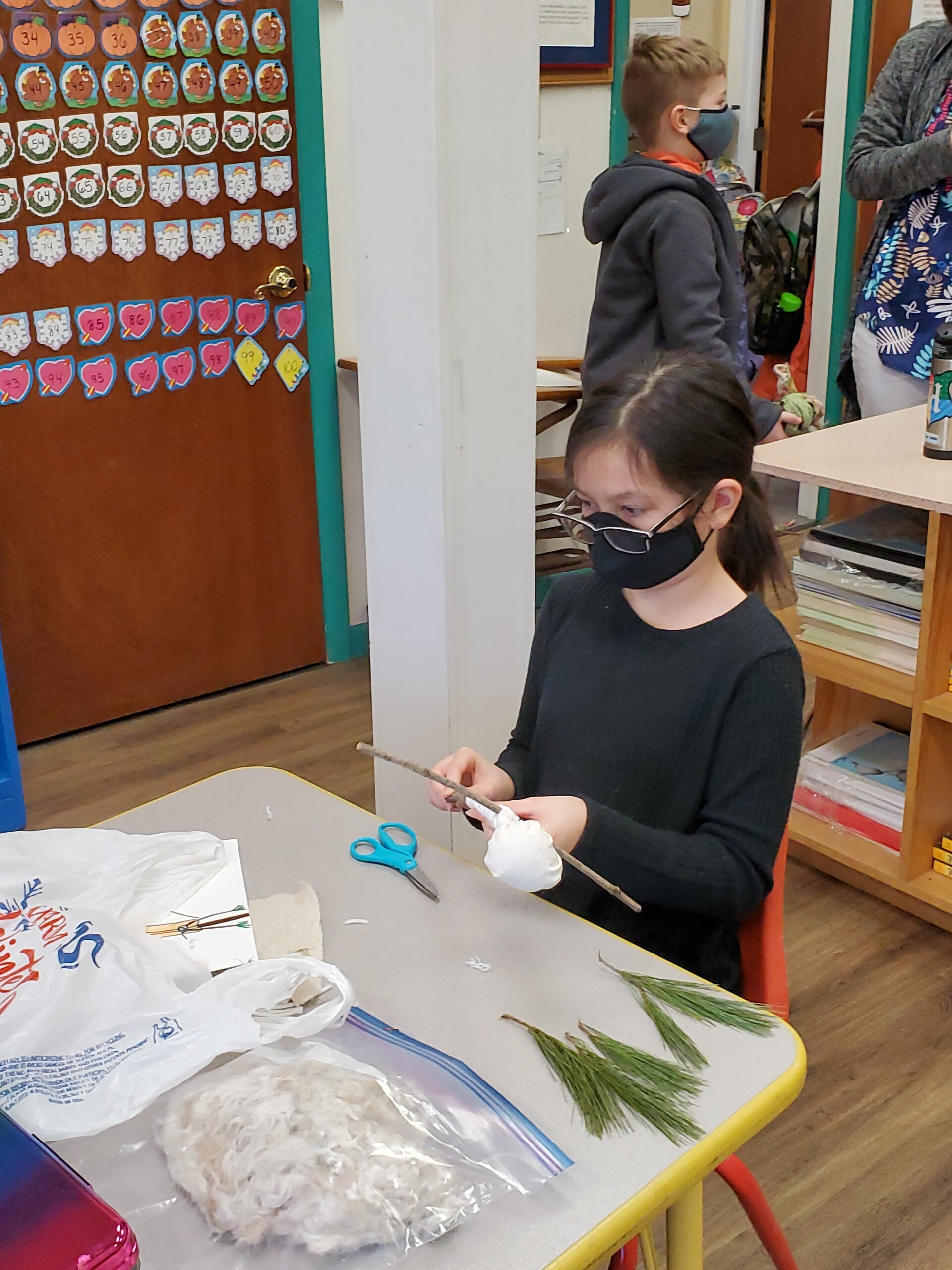 Student creating a scarecrow using sticks and branches