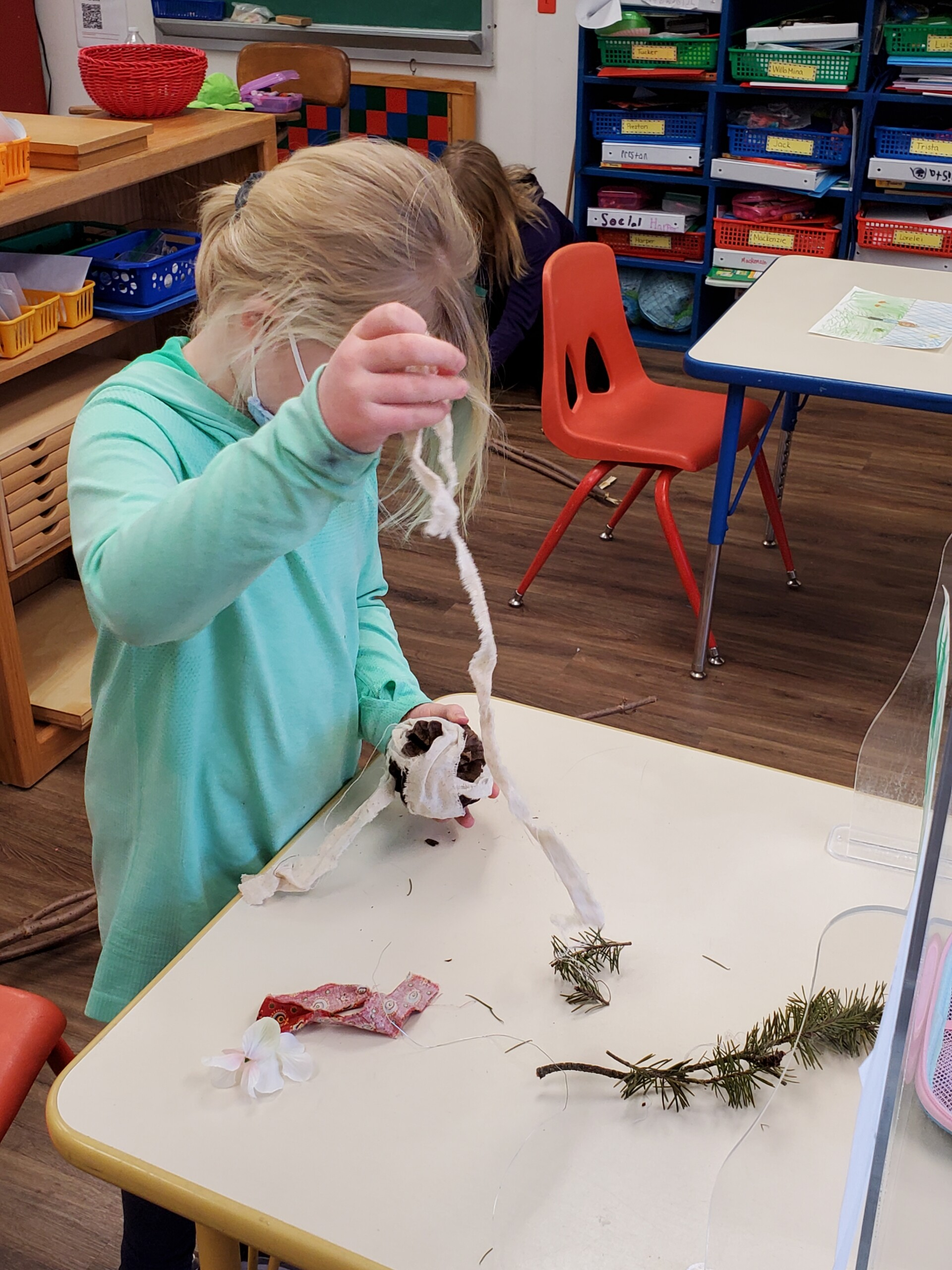 Student creating a scarecrow using cloth and branches